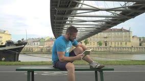 Mannen skrattar, läseboken och sitter på bänken mot floden lager videofilmer