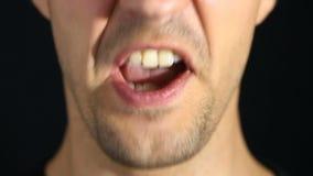 Mannen skriker in i kameran på en svart bakgrund Skvallra och grina närbilden stock video