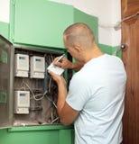 Mannen skrivar om läsningar för elektrisk meter Royaltyfri Foto