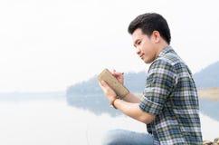 Mannen skriver en bok i parkera på en sommardag fotografering för bildbyråer