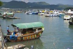 Mannen skriver in fiskebåten på den allsångKee hamnen i Hong Kong, Kina Royaltyfria Bilder