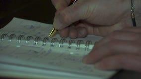 Mannen skriver i anteckningsboken hand och pennnärbild stock video