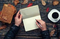 Mannen skriver i en anteckningsbok i parkera Royaltyfri Foto