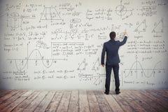 Mannen skriver lösningen av matematiska uppgifter på väggen Fotografering för Bildbyråer