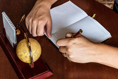 Mannen skriver med hans vänstersidahand i dagboktillträdena Arkivfoton
