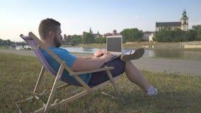 Mannen skriver på bärbara datorn som ligger på sunbed av floden arkivfilmer