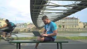 Mannen skriver på bärbara datorn som sitter på bänk mot floden lager videofilmer