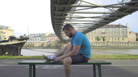 Mannen skriver på bärbara datorn som sitter på bänk mot floden, pannaskottet stock video