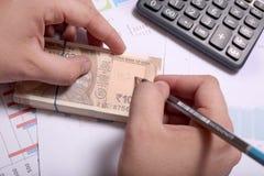 Mannen skriver på indier 10 rupie valutaanmärkningar med blyertspennan fotografering för bildbyråer
