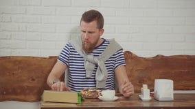 Mannen skriver på minnestavlan i kafé och äter efterrätten med kaffe arkivfilmer