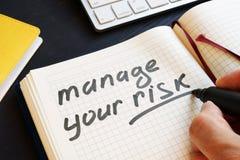 Mannen skriver rättan din risk i en anmärkning royaltyfria foton