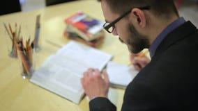 Mannen skriver till anteckningsboken lager videofilmer