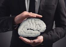 Mannen skyddar en hjärna med hans händer framförande 3d Royaltyfria Foton