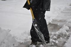 Mannen skyfflar snowa royaltyfria foton