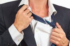 Mannen släpper loss hans band över closeupen för affärsdräkten Royaltyfri Foto