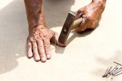Mannen slogg hans finger med en hammare Yrkesmässigt snickeri, träverk och folk begrepp av skadan i arbetsplatsen royaltyfria bilder
