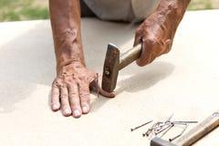 Mannen slogg hans finger med en hammare Yrkesmässigt snickeri, träverk och folk begrepp av skadan i arbetsplatsen arkivfoton