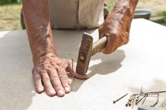 Mannen slogg hans finger med en hammare Yrkesmässigt snickeri, träverk och folk begrepp av skadan i arbetsplatsen arkivbilder