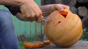 Mannen snider från en pumpastålar-nolla` - lykta i trädgården på en trädstubbe arkivfilmer