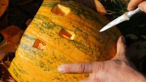 Mannen snider framsidan för en halloween pumpa Förbereda sig för höstferien arkivfilmer