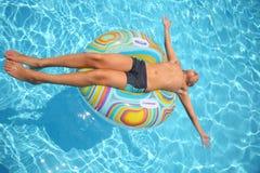 Mannen solbadar att ligga på en uppblåsbar leksak Arkivfoto