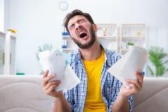 Mannen som är ilsken på räkningar som han behöver betala royaltyfri fotografi