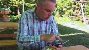 Mannen som äter och, tar foto på minnestavlan stock video