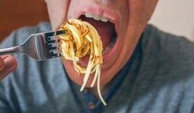 Mannen som äter spagetti med, avmaskar arkivfoton