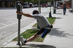 Mannen som övar sträcka gatan, parkerar metern royaltyfri foto