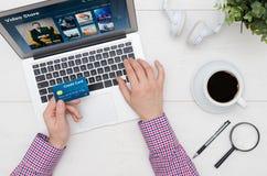 Mannen som använder kreditkorten för att betala för video på - begära service Royaltyfri Bild