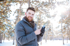 Mannen som använder smartphonen i vinter, parkerar Fotografering för Bildbyråer