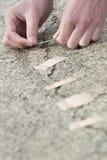 Mannen som applicerar bindemedel, förbinder på den spruckna vägen. Arkivfoto