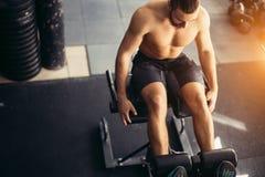 Mannen som att göra sitter, ups på bänken som arbetar på buk- muskler Arkivbilder