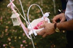 Mannen som bär den guld- klockan som får klar att kasta kronblad - bröllop ställa in garnering under mottagande - erbjuda rosa oc royaltyfria bilder