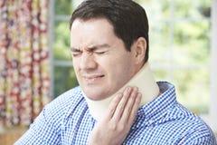 Mannen som bär den kirurgiska kragen smärtar in Arkivbilder