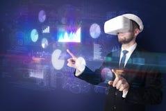 Mannen som bär VR, rullar med ögonen med diagram och rapporter Royaltyfri Fotografi
