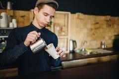 Mannen som baristaen förbereder läckert kaffe nära den construted väggen, är små skrivbordfyrkanter arkivfoto