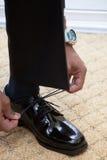 Mannen som binder skon, snör åt på svarta klänningskor Arkivbild