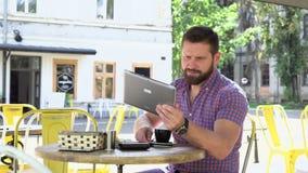 Mannen som bläddrar minnestavlan, dricker kaffe arkivfilmer
