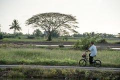 Mannen som cyklar till och med byn royaltyfri bild