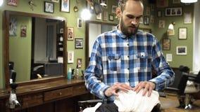 Mannen som den är förberedd för en traditionell rakning med en rakkniv i barberare, shoppar 4K lager videofilmer