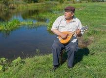 Mannen som den har, vilar på ett flodstrandsammanträde på en vide- stol som sjunger och spelar mandolinen Fotografering för Bildbyråer