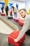 Mannen som en passagerare på bagagebältet väljer upp resväskor royaltyfri fotografi