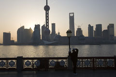 Mannen som gör Tai Chi, övar på bunden på gryning Shanghai arkivbild