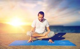 Mannen som gör yogaskalan, poserar utomhus arkivbild