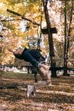 Mannen som hänger på ett säkerhetsrep som klättrar kugghjulet i ett affärsföretag, parkerar passerandehinder på repvägen, arboret royaltyfria bilder