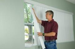 Mannen som hänger vertikala rullgardiner reparerar hem, underhåll Royaltyfri Fotografi