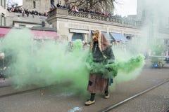 Mannen som häxa med gräsplan rök-bombarderar på karnevalet Arkivbild