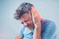 Mannen som har örat, smärtar att trycka på hans smärtsamma huvud på grå färger royaltyfri foto