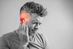 Mannen som har örat, smärtar att trycka på hans smärtsamma huvud som isoleras på grå färger royaltyfri foto